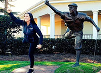 Lisa Vlooswyk poses with Payne Stewart Statue.